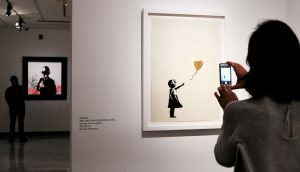 """Girl with Balloon, Gold"" by Banksy [Image via New York Times]"