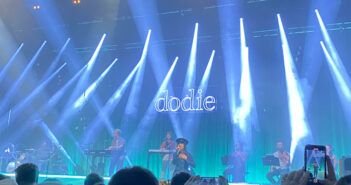 Dodie stands with her hand on her heart, wearing her 'Hate Myself' music video costume on a stage illuminated in blue. Behind, her band and a light up sign which reads 'dodie'.